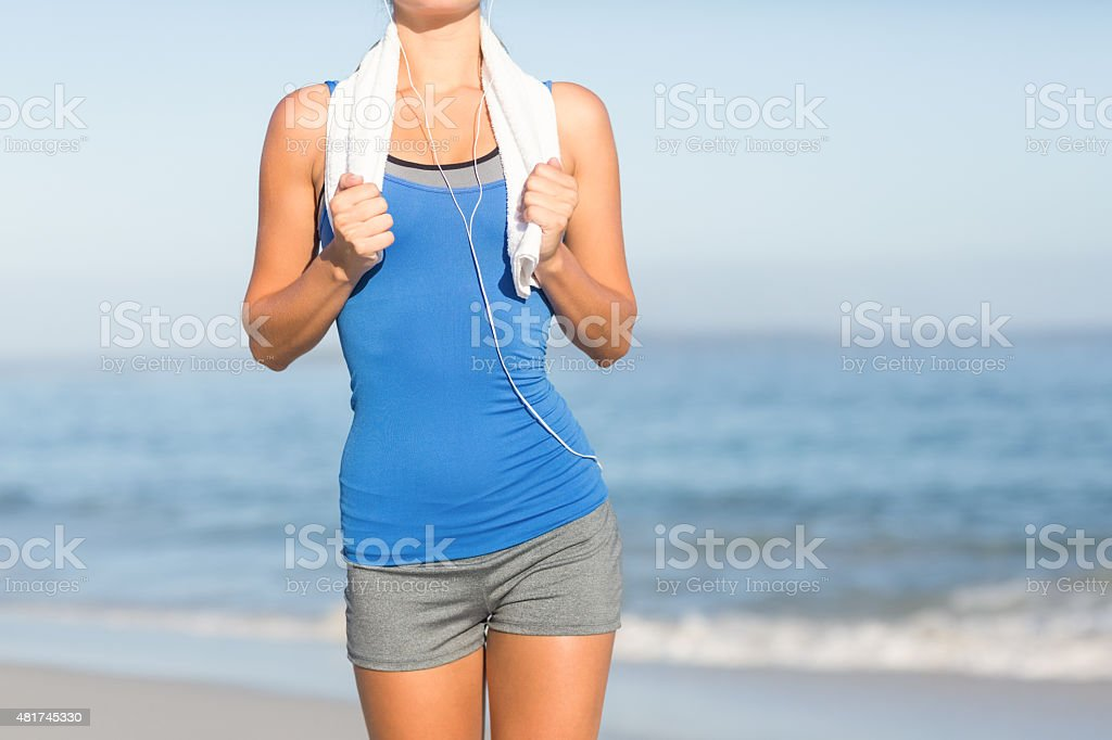 Fit woman running with towel around neck stock photo