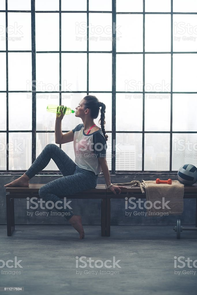 Fit woman sitting on bench in loft gym drinking water stock photo