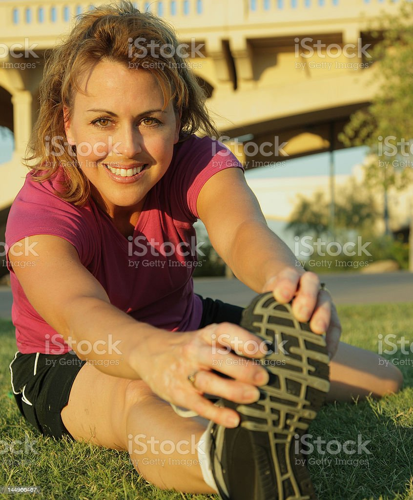 Fit woman stretches before exercise royalty-free stock photo