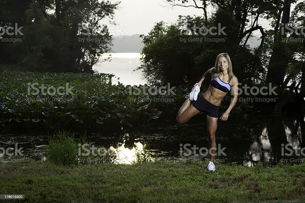 Fit woman stretching in a park at sunrise royalty-free stock photo