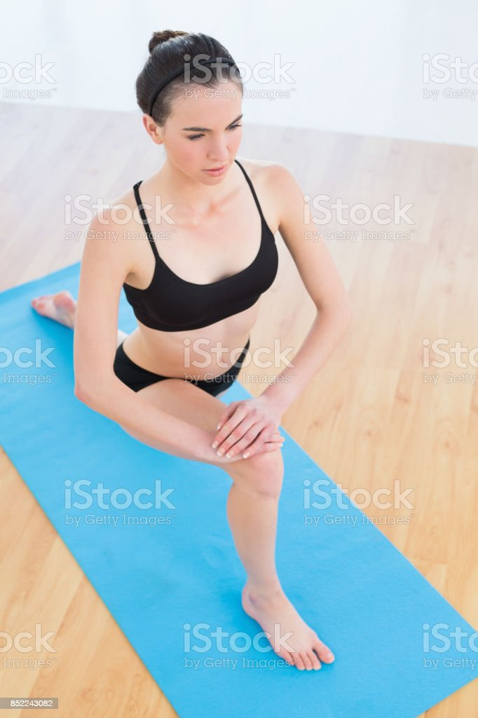 Fit woman stretching leg in fitness center stock photo