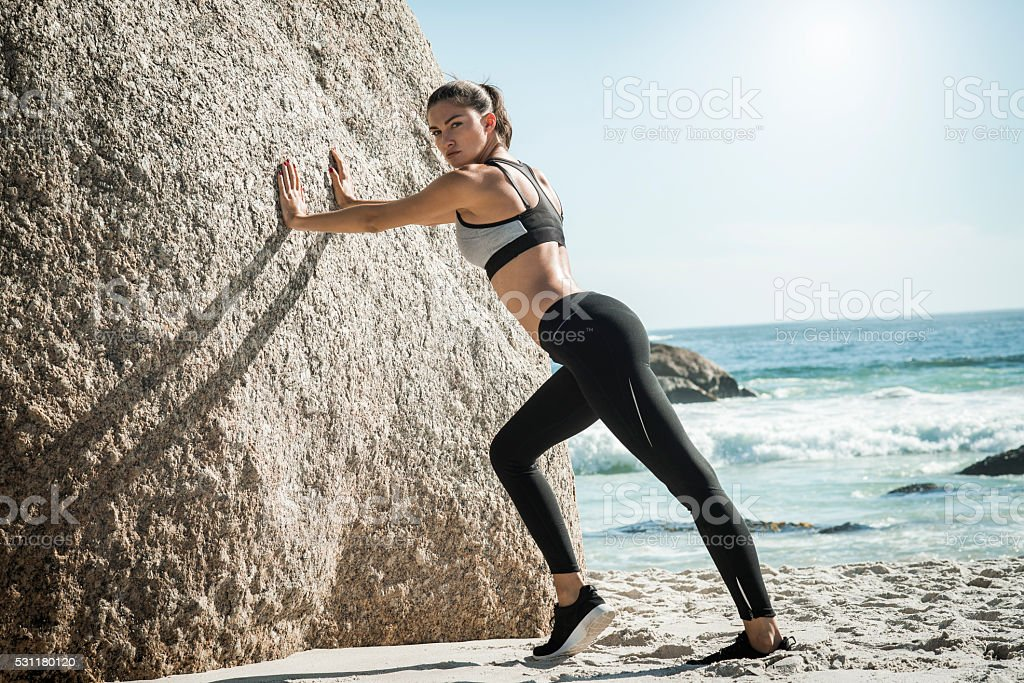 fit woman stretching on the beach stock photo