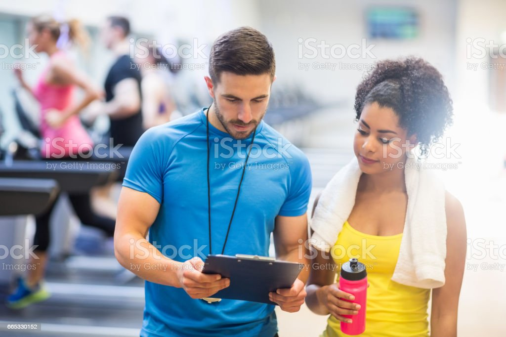 Fit woman talking to her trainer stock photo