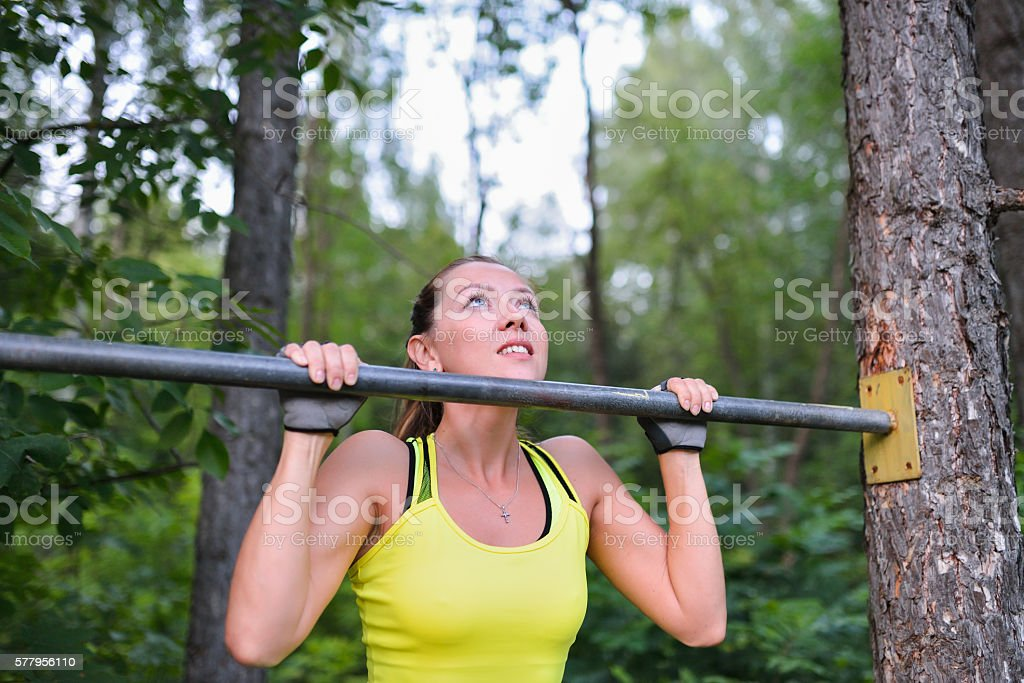 Fit woman training pull ups on horizontal bar in city stock photo