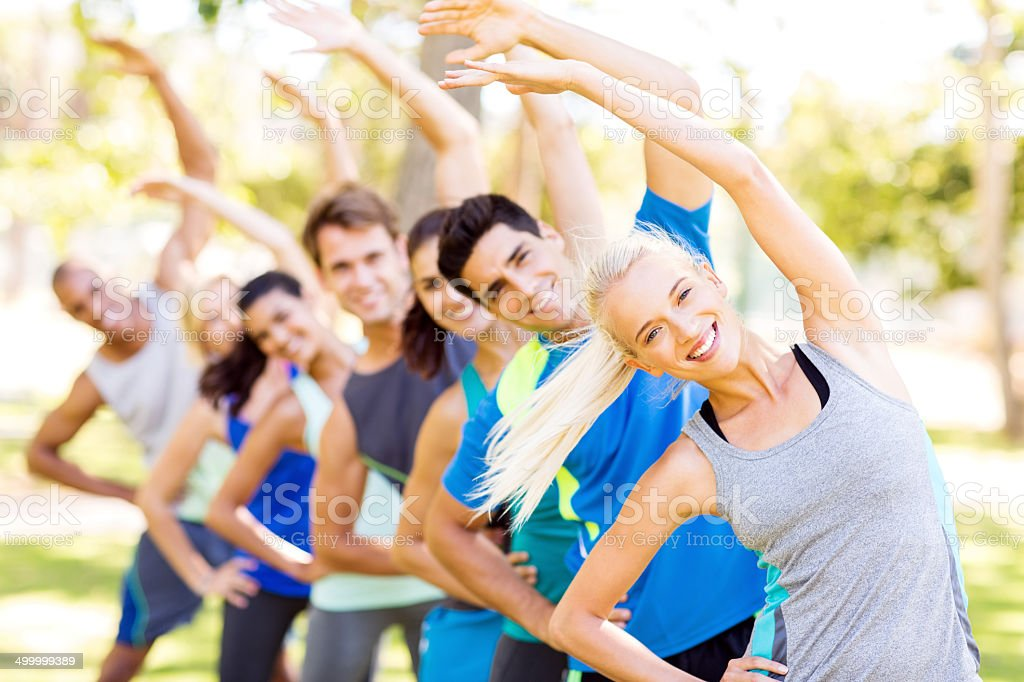Fit Woman With Friends Exercising At Park stock photo