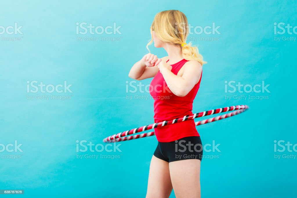 Fit woman with hula hoop doing exercise stock photo