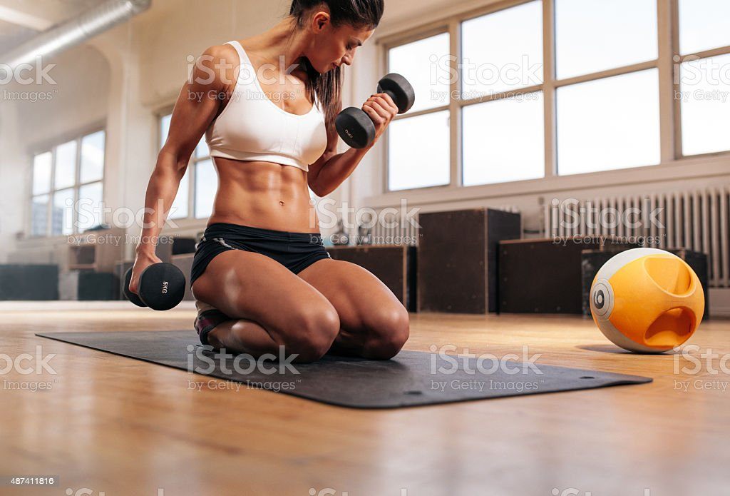 Fit woman working out at the gym with dumbbells stock photo