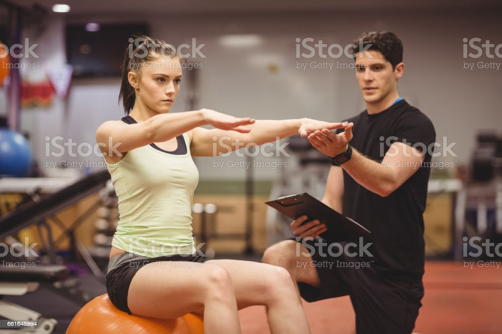 Fit woman working out with trainer stock photo