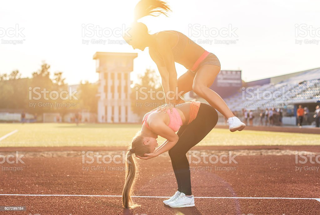 Fit women at the stadium playing leap frog. stock photo