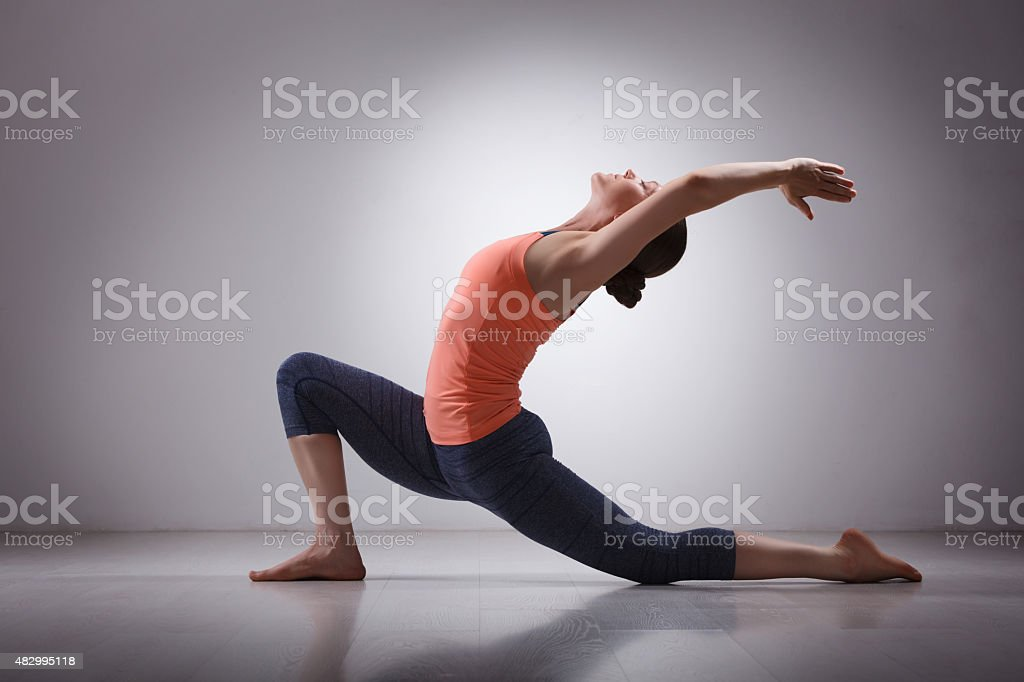 Fit yogini woman practices yoga asana  Anjaneyasana stock photo