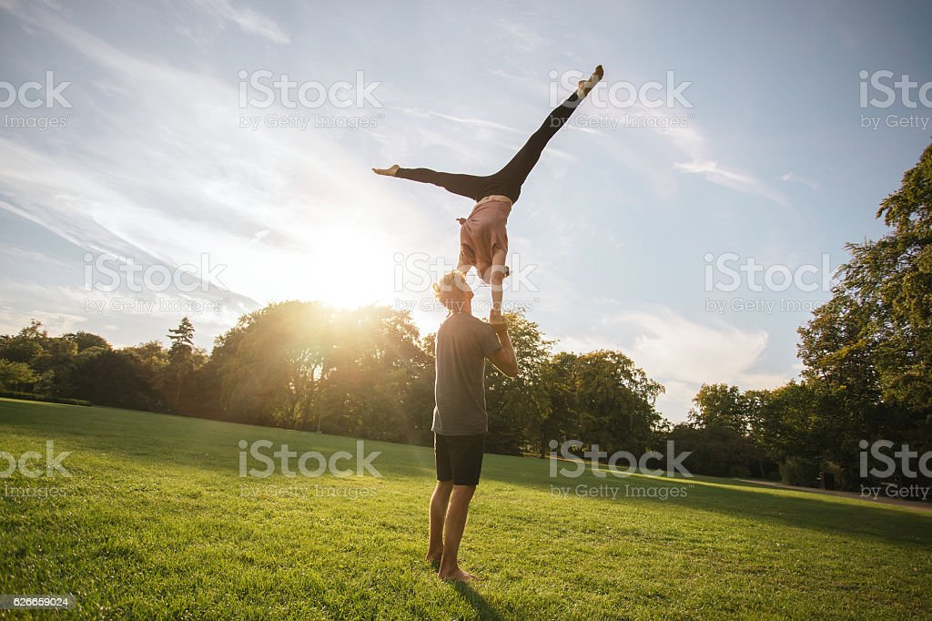 Fit young couple doing acro yoga in park stock photo