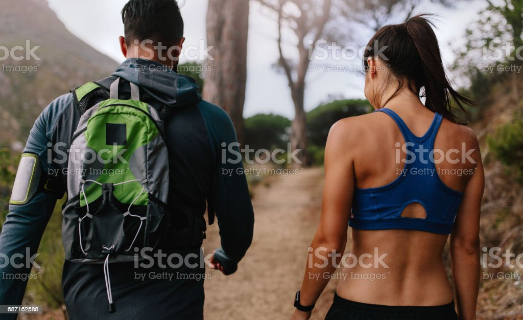 Fit young couple walking on mountain trail stock photo