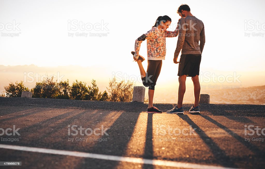 Fit young couple warming up before a run together stock photo