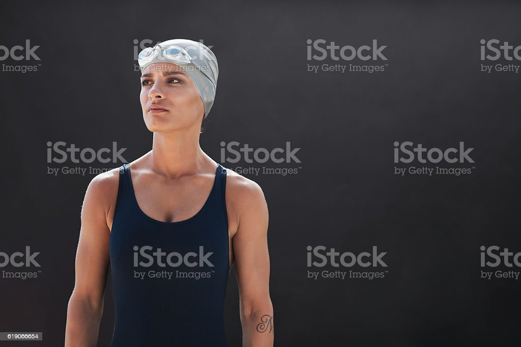 Fit young female swimmer looking away stock photo