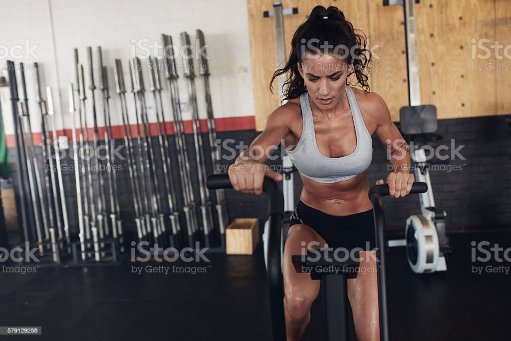 Fit young female working out on gym bike stock photo