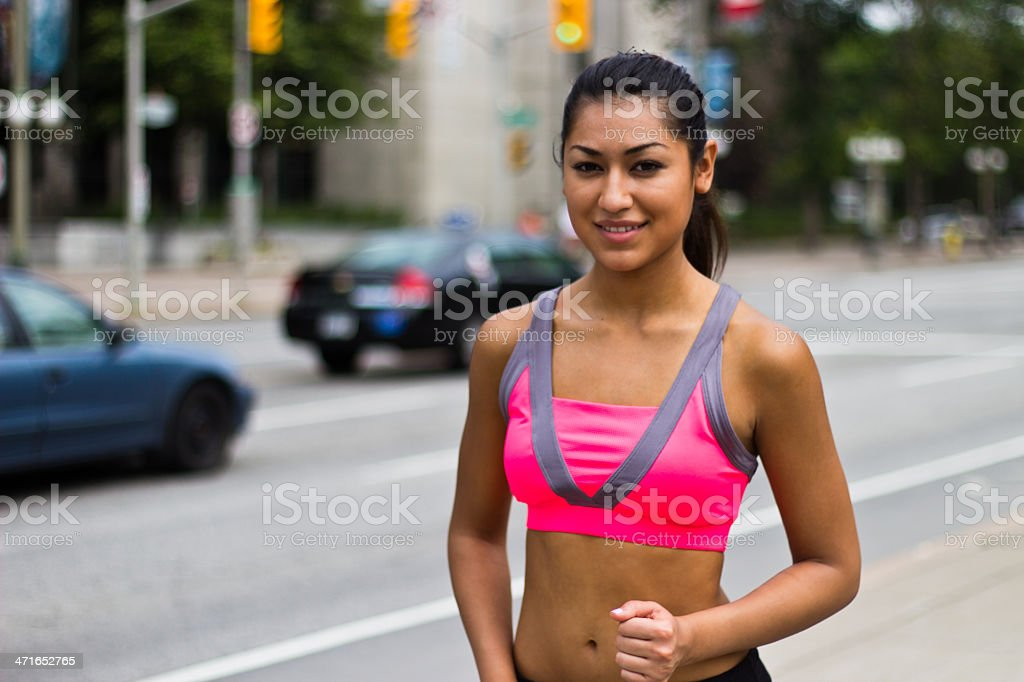 Fit young hispanic woman running along a busy city street royalty-free stock photo