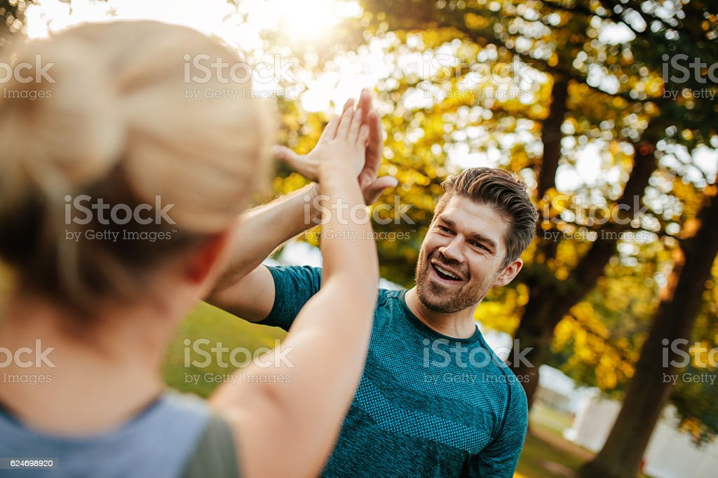 Fit young man giving high five to woman stock photo