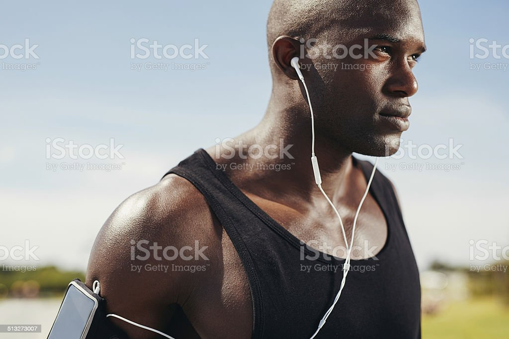 Fit young man wearing earphones stock photo