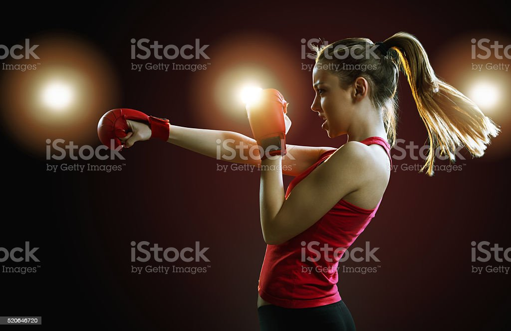 Fit, young woman boxing, black background, back light stock photo