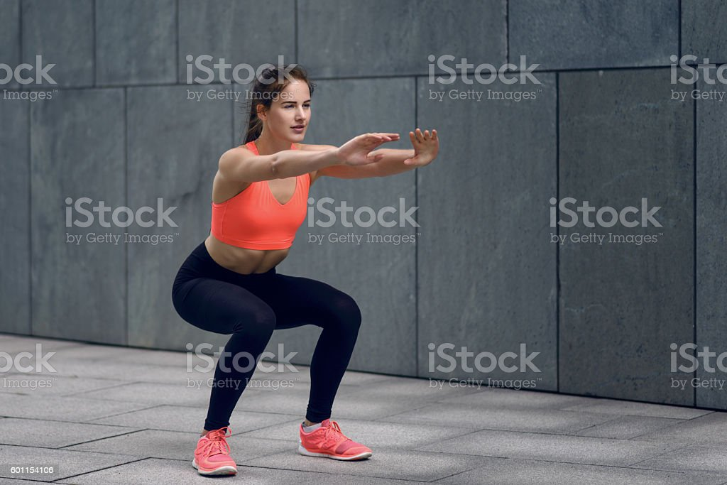Fit young woman doing squats stock photo