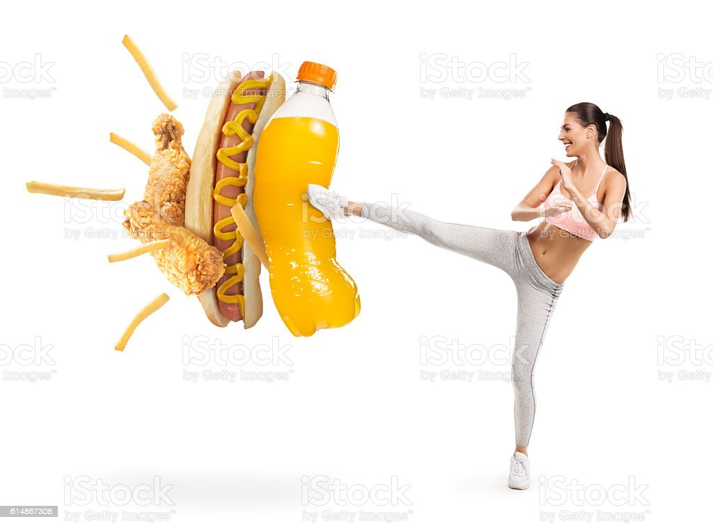 Fit young woman fighting off soda and junk food stock photo