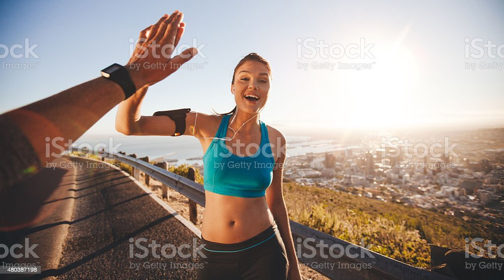 Fit young woman high fiving her boyfriend after a run stock photo