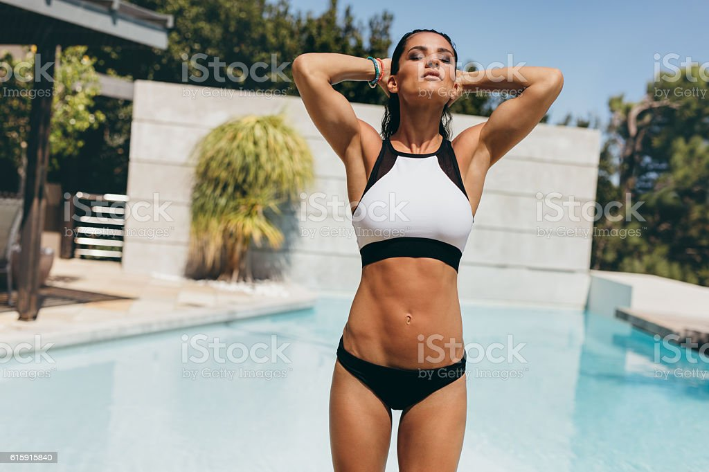 Fit young woman in swimwear at the poolside stock photo