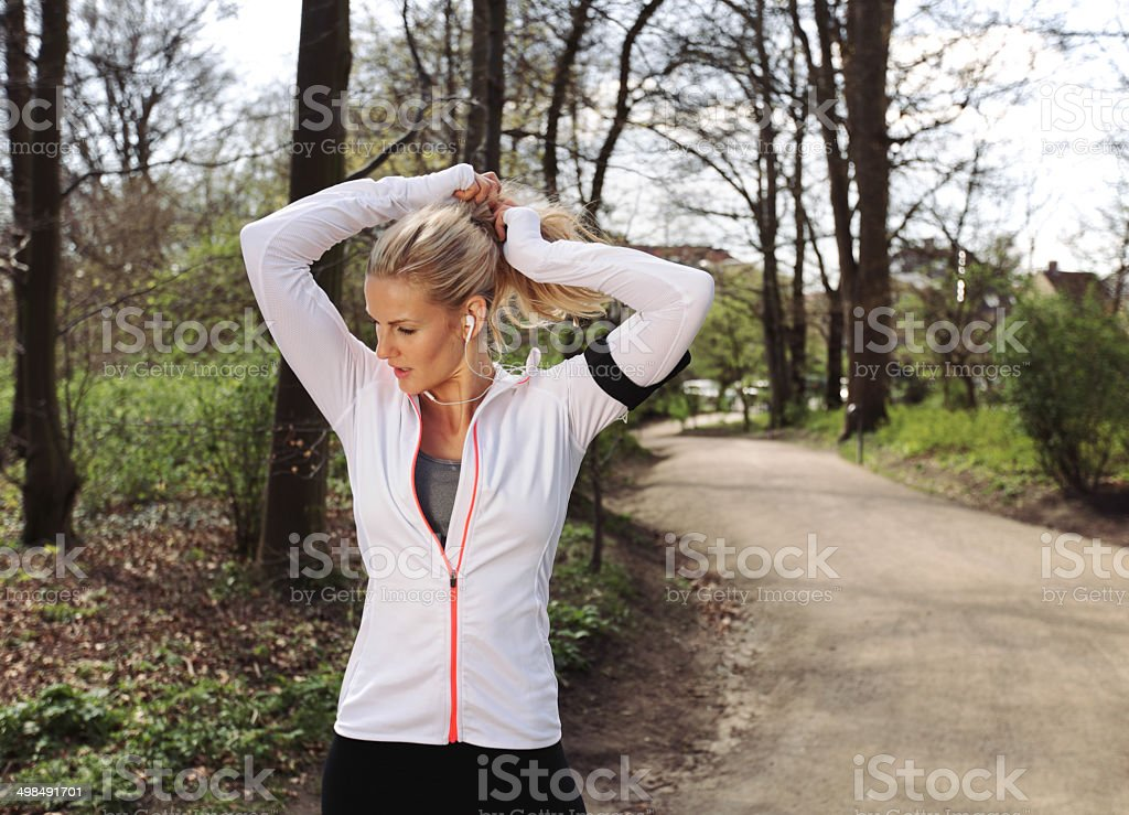 Fit young woman preparing for her run in forest stock photo