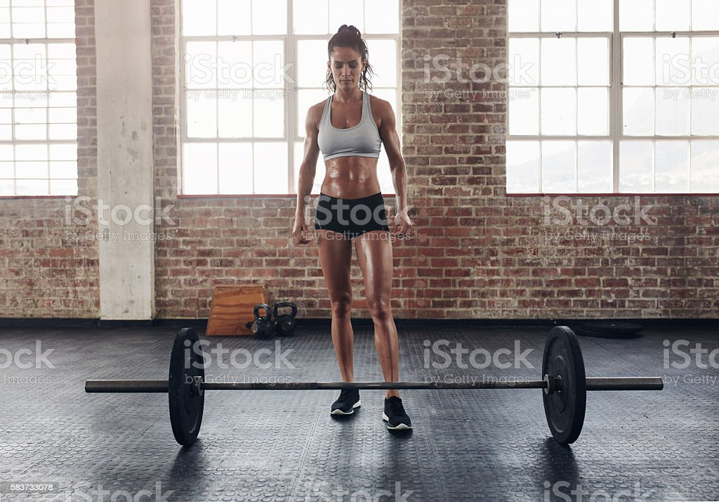 Fit young woman standing at gym with barbells on floor stock photo