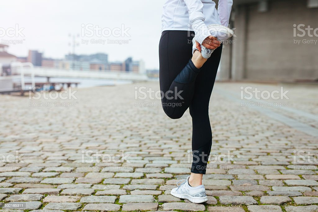 Fit young woman stretching her leg before a run stock photo