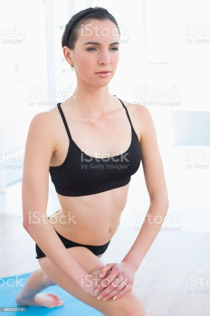 Fit young woman stretching leg in fitness center stock photo