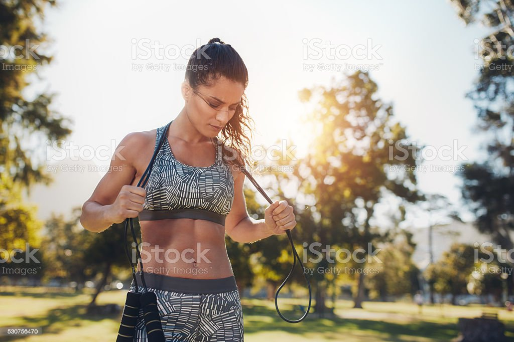 Fit young woman with a skipping rope at the park stock photo