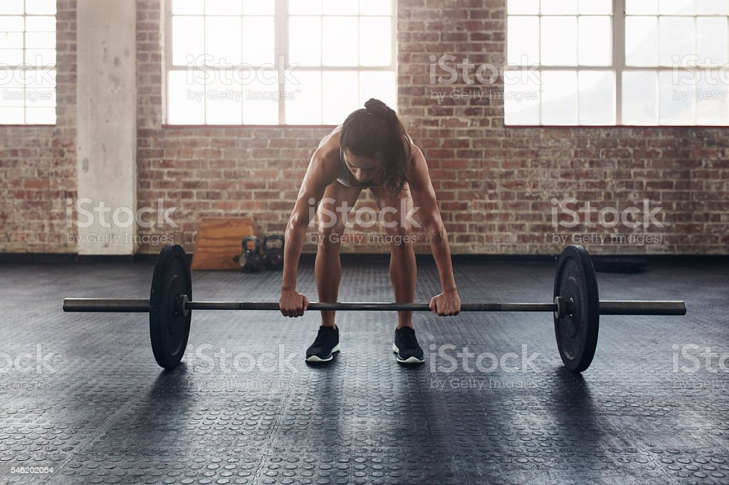 Fit young woman working out with a barbell stock photo