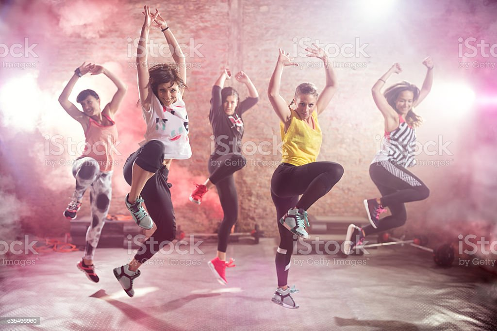Fit young women dancing  and exercising stock photo