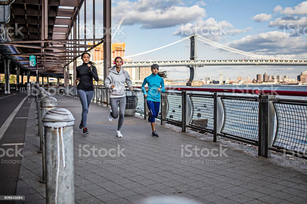 Fit young women running on promenade stock photo