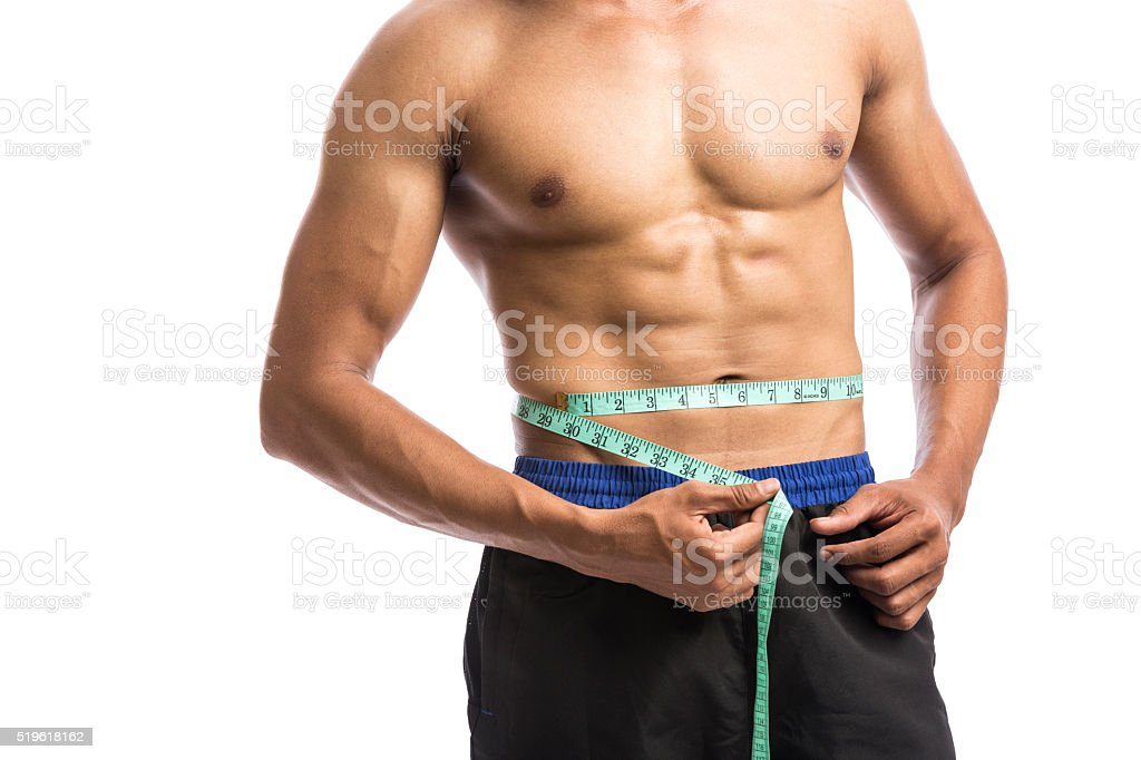 Fitiness trainer man measuring his waist stock photo