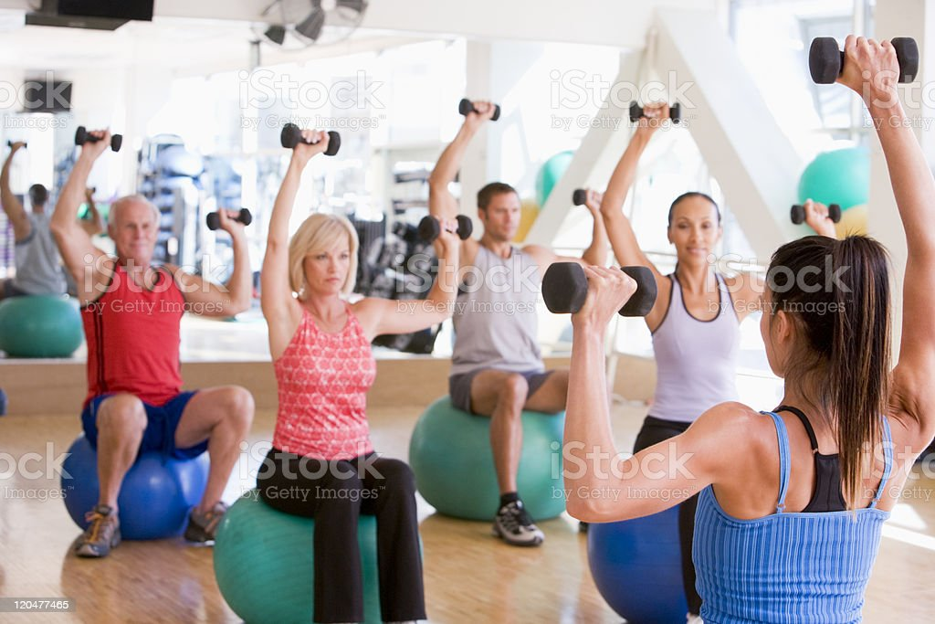 Fitness class at a gym using dumbbells and balls stock photo