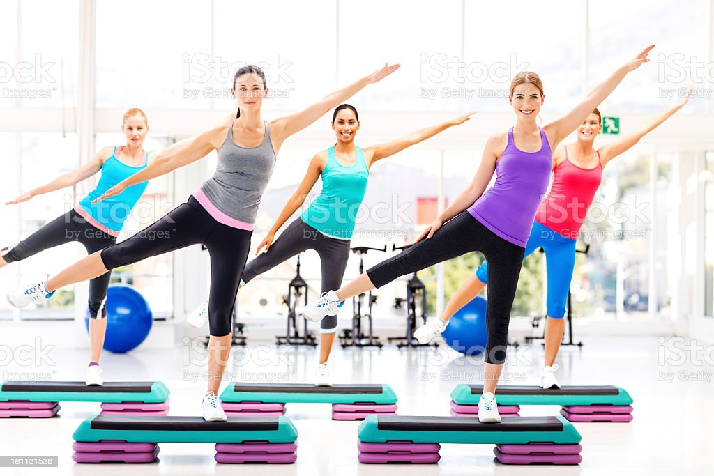 Fitness Class Doing Aerobics On Steps In Health Club stock photo