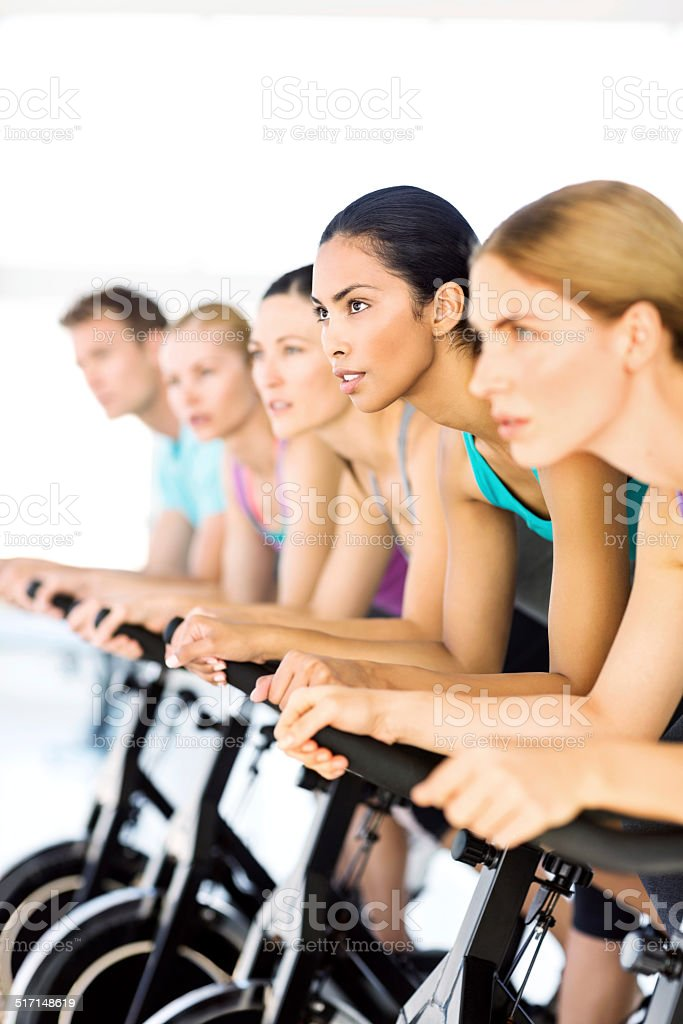 Fitness Class Exercising On Spin Bikes In Health Club stock photo