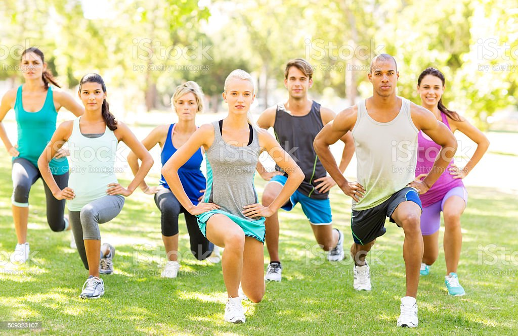 Fitness Class Performing Stretching Exercise In Park stock photo