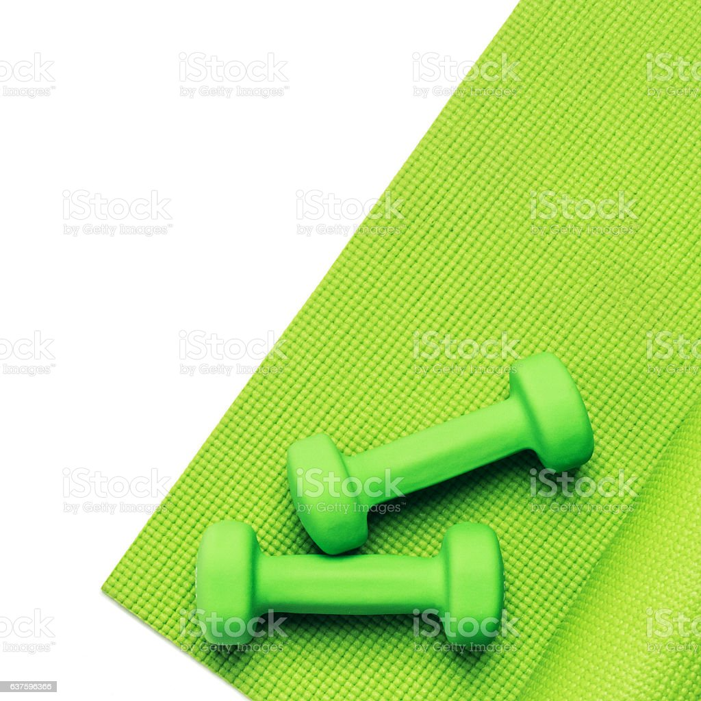 Fitness concept - green yoga mat and dumbbells stock photo