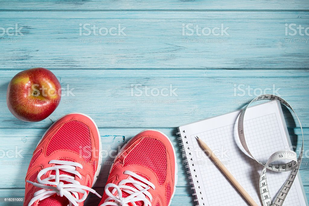 Fitness concept, pink sneakers, apple and notebook and measuring tape stock photo