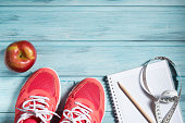 Fitness concept, pink sneakers, apple and notebook and measuring tape