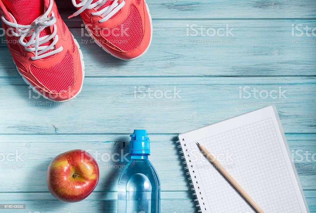 Fitness concept, pink sneakers, apple, bottle of water and notebook stock photo
