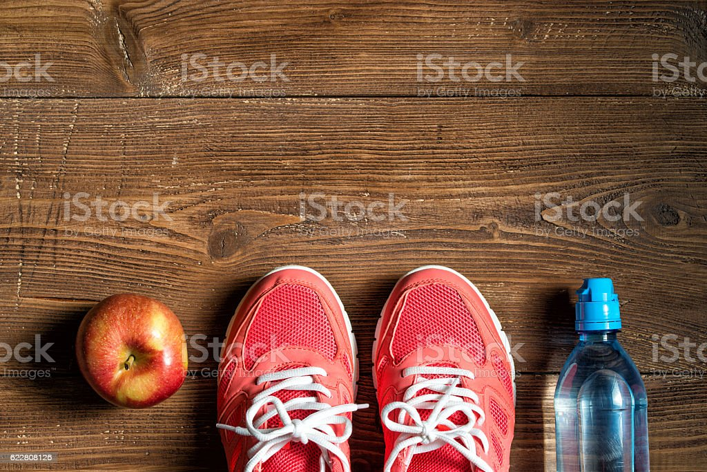 Fitness concept, pink sneakers, red apple and bottle of water stock photo