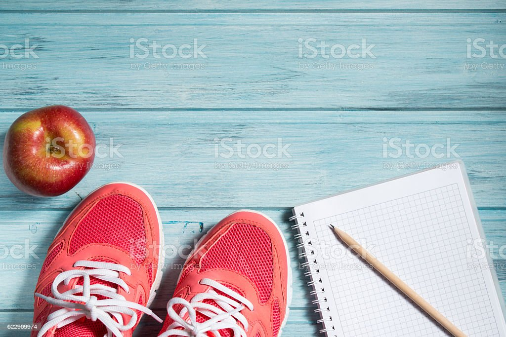 Fitness concept, pink sneakers, red apple and notebook with pencil stock photo
