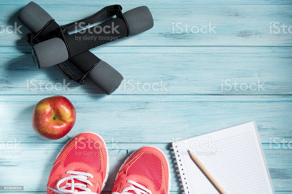 Fitness concept, pink sneakers, red apple, dumbbells and notebook stock photo