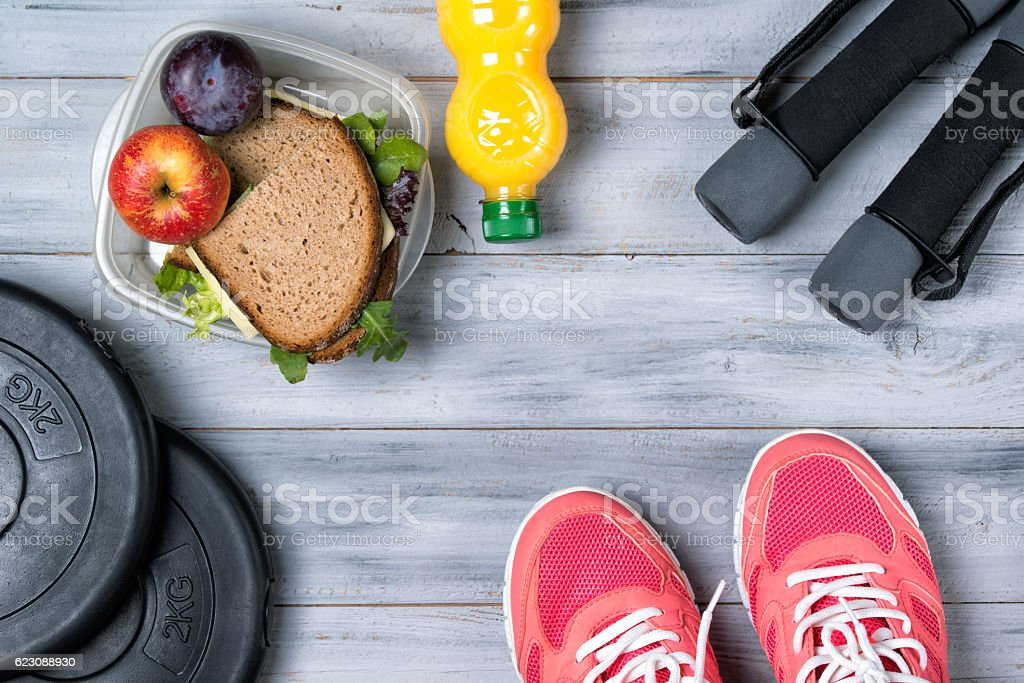 Fitness concept, pink sneakers, weight plates, dumbbells, sandwich stock photo