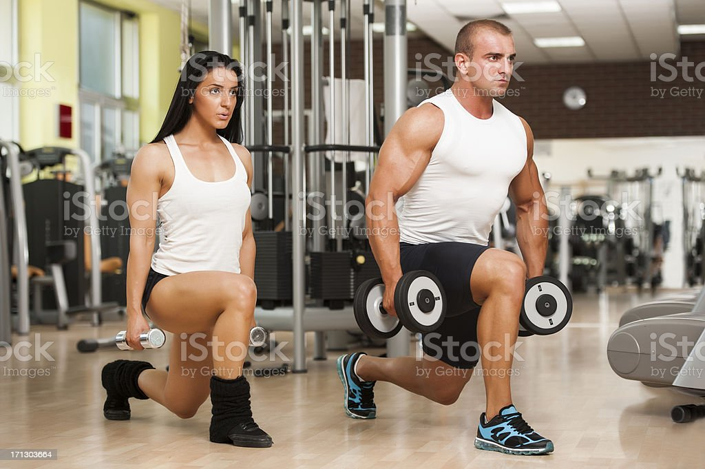 Fitness Couple Doing Lunges With Hand Weights stock photo