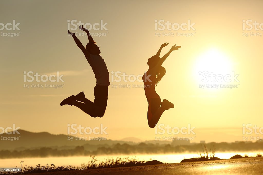 Fitness couple jumping happy at sunset stock photo